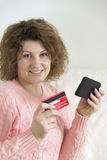 adult woman makes a purchase from your mobile phone by credit card Stock Photo