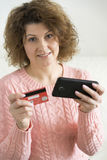 adult woman makes a purchase from your mobile phone by credit card Royalty Free Stock Image
