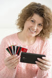 adult woman makes a purchase from your mobile phone by credit card Stock Photos