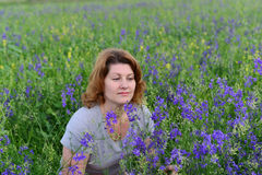 Adult woman in meadow with wild flowers Stock Images