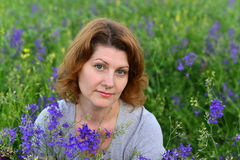 Adult woman in meadow with wild flowers Stock Photo