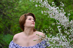 Adult woman near the cherry blossoms Royalty Free Stock Image