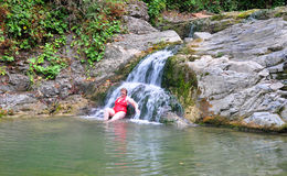 Adult woman near a waterfall Royalty Free Stock Photography