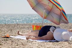 Adult woman overweight on the beach. Adult woman  overweight on the beach under an umbrella Royalty Free Stock Image