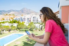 Woman using mobile in the terrace next to pool Stock Images