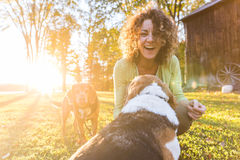 Adult woman playing with her dogs at park. Or in the backyard. Autumn colors, unstaged situation with candid model and playful dogs. Lifestyle and friendship Stock Images