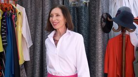 Adult Woman Posing in Blouse in Fitting Room Store. Aged Lady Wearing White Shirt and Skirt in Boutique. Elderly Female Shopping in Fashion Shop. Smiling Buyer stock video