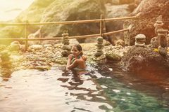 Free Adult Woman Posing With A Smile In The Sun And A Thermal Spring On The Background Of Rocks Royalty Free Stock Image - 140059116