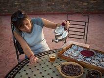 Adult woman pours tea Stock Photography