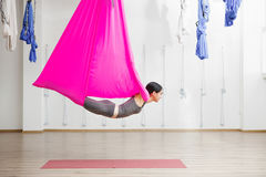 Adult woman practices anti-gravity yoga position in gym. Aerial antigravity yoga girl on pink silk hammock, doing exercises, meditating in calm position of Stock Photos