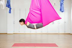 Adult woman practices anti-gravity yoga position in gym. Aerial antigravity yoga girl on pink silk hammock, doing exercises, meditating in calm position of Royalty Free Stock Photos