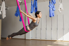Adult woman practices inversion anti-gravity yoga position in gym. Stock Photos