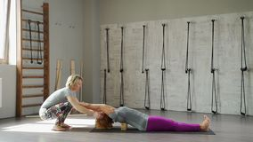 An adult woman practices yoga, using professional equipment stock video
