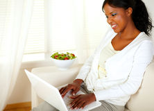 Adult woman with a pretty smile, working on laptop Royalty Free Stock Photos
