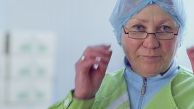 Adult woman in protective cap turns to camera and removes eyeglasses from face. Portrait of factory worker. Prores codec stock video
