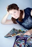 Adult woman reading comics books. A grown up woman reads some comic book laying down royalty free stock images