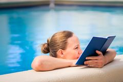 Adult woman reading interesting book in a pool in beautiful sunny day.  royalty free stock photos