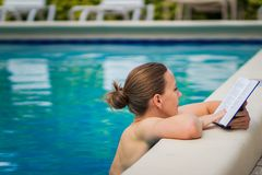 Adult woman reading interesting book in a pool in beautiful sunny day.  royalty free stock image