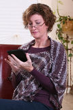 Adult woman reading a tablet. Adult woman thinking relaxing reading a tablet Royalty Free Stock Photo