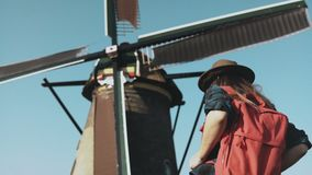 Adult woman walks up to a rustic windmill. Incredible cinematic low angle. Local girl in hat looks at farm mill. 4K. Adult woman with red backpack walks up to stock video footage