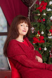 Adult woman in a red sweater against Christmas tree Royalty Free Stock Photos
