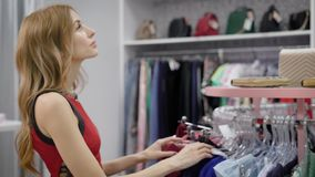 Adult woman with red wavy hair is going over hall of clothing shop, thinking and looking for best dress. Touching garments on racks stock footage