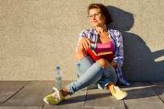 Adult woman relaxing sit on the sidewalk. Royalty Free Stock Photography