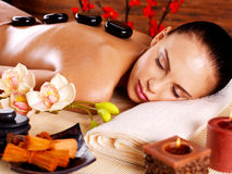 Adult woman relaxing in spa salon with hot stones on back Stock Images