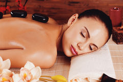 Adult woman relaxing in spa salon with hot stones on back Stock Photography