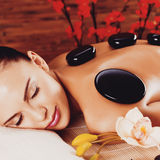 Adult woman relaxing in spa salon with hot stones on back Royalty Free Stock Images