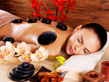 Adult woman relaxing in spa salon with hot stones on back Royalty Free Stock Photos