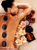 Adult woman relaxing in spa salon with hot stones on body. Beauty treatment therapy Stock Photo