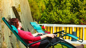 Adult woman relaxing on sunbed in garden. Woman relaxing on sunbed or deck chair in her garden during sunny weather Royalty Free Stock Photos