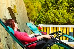 Adult woman relaxing on sunbed in garden. Woman relaxing on sunbed or deck chair in her garden during sunny weather Stock Photography