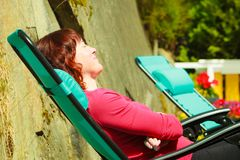 Adult woman relaxing on sunbed in garden. Woman relaxing on sunbed or deck chair in her garden during sunny weather Stock Image