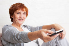 Adult woman with remote control. Female looking tv Stock Images
