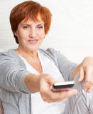 Adult woman with remote control Royalty Free Stock Images