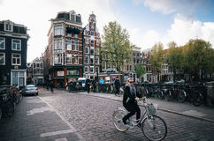 Adult woman rides a bicycle in historical part of Amsterdam with typical traditional houses. Royalty Free Stock Image