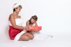 Adult woman in Santa costume and smiling little girl Royalty Free Stock Photos
