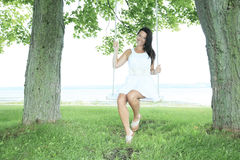 Adult woman sit on a swing Stock Image