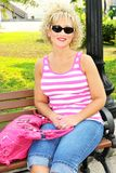 Adult woman siting on a park bench with pink purse Royalty Free Stock Images