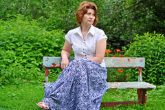 Adult woman sitting on a bench in the garden Stock Photo