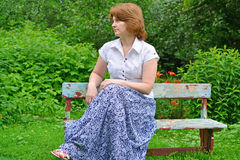 Adult woman sitting on a bench in the garden Royalty Free Stock Images