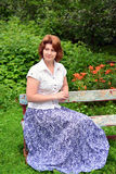 Adult woman sitting on a bench in the garden Royalty Free Stock Image