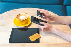 Adult woman sitting in cafe and using cellular, tablet and bank credit card stock photo