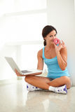 Adult woman sitting with laptop and donut on hands Royalty Free Stock Photo