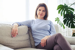Adult woman sitting on sofa in bright living room Royalty Free Stock Image