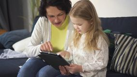 Adult woman is sitting on sofa and teaching little girl using new digital technology. stock video footage