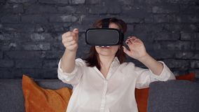 Adult woman is sitting on sofa and using new digital technology of augmented 3d reality simulation. stock footage