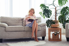 Adult woman smiling while turning page of book Royalty Free Stock Photography